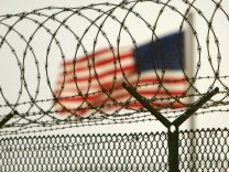 American flag waves within the razor wire-lined compound of Camp Delta prison, at the Guantanamo Bay U.S. Naval Base