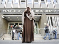 Kenza Drider, a French Muslim of North African descent, wearing a niqab, leaves the police station after their release in Paris