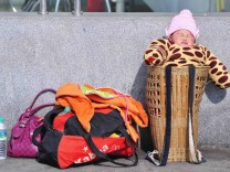 A baby sits in a basket while waiting to board a train at a railway station in Nanjing