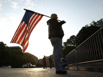 Man holds a U.S.  flag outside the White House in Washington