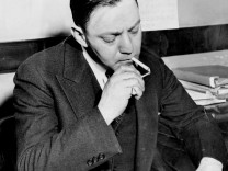 A study in nonchalance. Dutch Schultz lights a cigarette dur