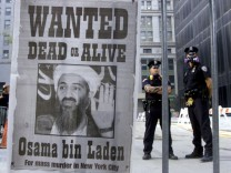 File photo of police standing near a wanted poster of Saudi-born militant Osama bin Laden in New York