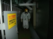 A worker walks through Tokyo Electric Power's Fukushima Daiichi Nuclear Power Plant's Unit 1 reactor in Fukushima prefecture in this handout photo released by TEPCO