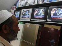 A man watches Pakistan's Prime Minister Yusuf Raza Gilani on a televised address to the parliament at an appliance store in Islamabad