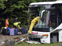 Firefighters and road workers retrieve luggages from the wreckage of a bus near Kranj