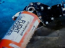 File image published on the website of France's BEA air accident inquiry office shows the orange cylindrical flight data recorder above the sand