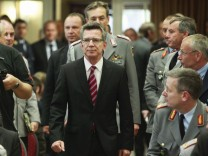 German Defence Minister de Maiziere arrives in hall of Julius-Leber army base to present his reform plans of German armed forces officers in Berlin