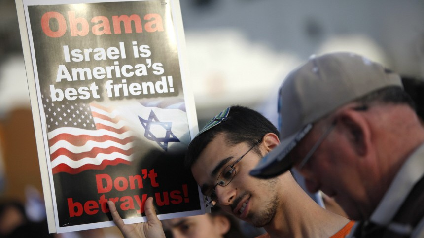 An Israeli holds a sign during a protest in front of the U.S. embassy in Tel Aviv