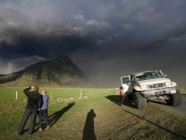 People look at the ash plumes from Iceland's Eyjafjallajokull volcano