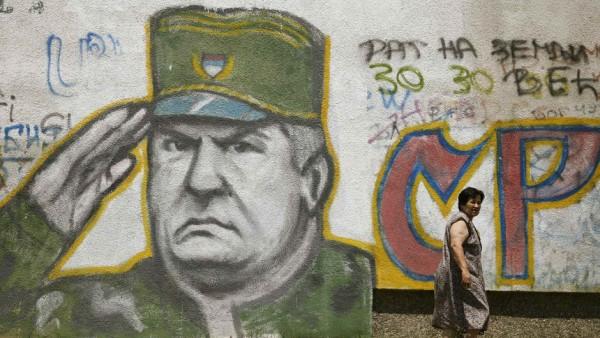 A woman walks past graffiti of Bosnian Serb fugitive general Ratko Mladic in Belgrade
