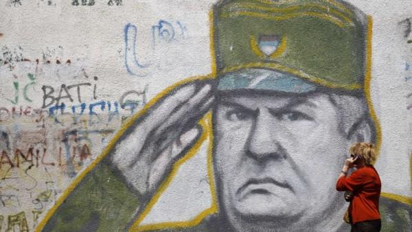 Woman walks past graffiti of Bosnian Serb wartime general Mladic in a suburb of Belgrade