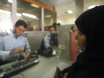 A Hamas policeman stamps the passport of a Palestinian woman at the Rafah border crossing in the southern Gaza Strip