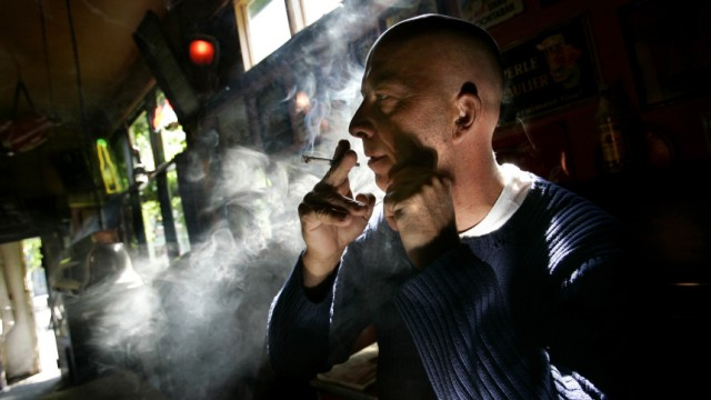 Unidentified man smokes marijuana joint in a coffeeshop in Rotterdam