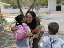 A schoolgirl hugs her teacher Martha Ivette Rivera Alanis before starting clashes at school in a working class neighbourhood in Monterrey