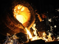 A labourer pours molten iron into the cast for the shell of a water pump at a water pump factory in Yingtan