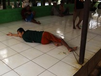 A mental patient lies on the floor during lunchtime at the Galuh foundation compound in East Bekasi