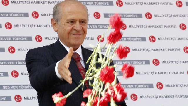 MHP leader Devlet Bahceli hands out carnations during an election rally in Ankara