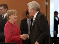 German Chancellor Angela Merkel shakes hands with Baden-Wuerttemberg  State Premier Kretschmann before meeting in Berlin