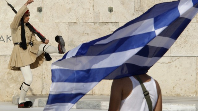 A protester holds a Greek flag as a Greek Presidential guard marches at the monument of the unknown soldier in Athens