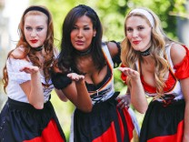 Models pose in a traditional Bavarian dress designed as so-called 'World Cup' dirndl in Munich