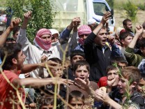 Syrians shout slogans in favour of Turkey as they wait to cross on the Syrian side of the border zone between the two countries near Guvecci
