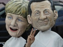 Oxfam's activists wear masks depicting EU leaders during a protest called ' A working lunch for nine billion'  outside the European Parliament in Brussels
