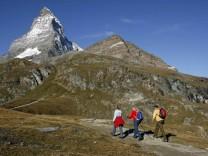 Matterhorn in der Schweiz: Hikers walk near the Matterhorn mountain above the village of Zermatt