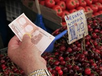 A Greek man pays for fruit and vegetables at the main food market in central Athens