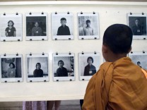CAMBODIAN MONK LOOKS A PICTURES OF KHMER ROUGE VICTIMS IN FORMER TORTURE CENTRE