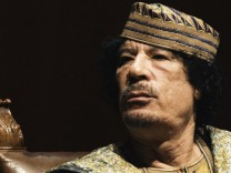 Libyan leader Gaddafi gestures as he attends a meeting with a business women delegation hosted by Italy's minister of Equal Opportunities Garfagna at the Auditorium Hall in Rome