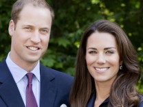 Britain's Prince William and Catherine, Duchess of Cambridge pose for the official tour portrait for their trip to Canada and California, in the gardens of Clarence House in London