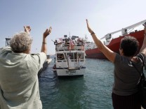 People wave as 'The Audacity of Hope', a U.S. boat which is part of a small flotilla, sails in Perama port near Athens
