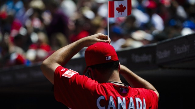 Blue Jays pitcher Villanueva puts a Canadian flag in his hat while his team plays the Phillies during their MLB Interleague baseball game in Toronto