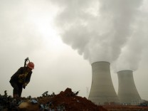 A worker searches for usable things at a garbage dump site near a power plant in Yingtan,