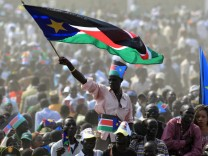 A man waves South Sudan's national flag as he attends the Independence Day celebrations in the capital Juba