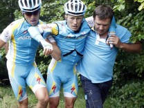 Astana rider Vinokourov of Kazakhstan (C) is carried by teammates after a fall during the ninth stage of the Tour de France 2011 cycling race from Issoire to Saint-Flour