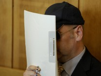 Defendant Olaf H. covers his face as he sits in the regional court in Krefeld