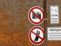 Signs forbidding photography and mobile phones are pictured on construction site fence of new headquarters of Germany's intelligence agency Bundesnachrichtendienst  in Berlin