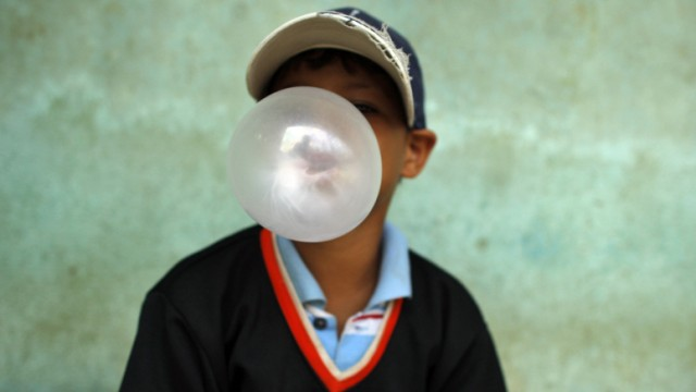 A child blows a bubble gum as he attends a donation of baseball equipments organized by Homerun hopefuls in Santo Domingo