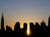 The sun sets over Manhattan aligned exactly with the streets in a phenomenon known as 'Manhattanhenge', in New York