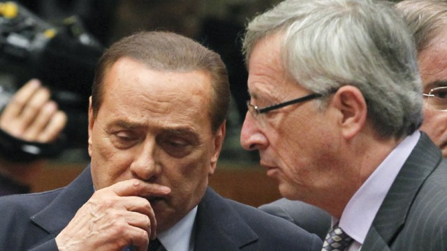 Italy's Prime Minister Berlusconi talks with Luxembourg's Juncker at the start of an EU leaders summit in Brussels