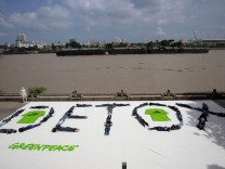 Greenpeace activists form a human banner with message 'Detox' at Santichaiprakarn Park, on the banks of Chao Phraya river in Bangkok