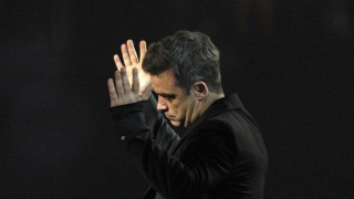 Robbie Williams of Take That reacts after the band won best British group during the BRIT music awards at the O2 Arena in London