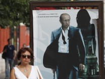 People walk past an advertising hoarding overlaid with a poster of Russia's Prime Minister Vladimir Putin posing as a secret agent in Moscow