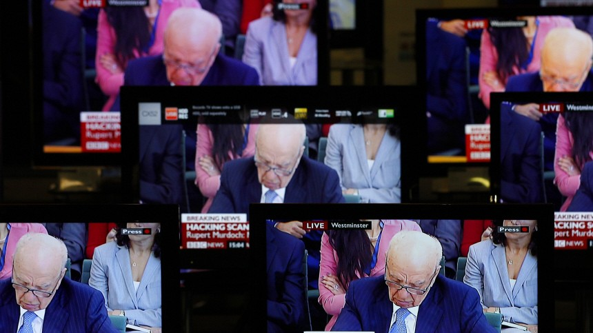 News Corp Chairman and Chief Executive Rupert Murdoch is seen on television screens in an electrical store as he is questioned by a parliamentary committee on phone hacking, in Edinburgh