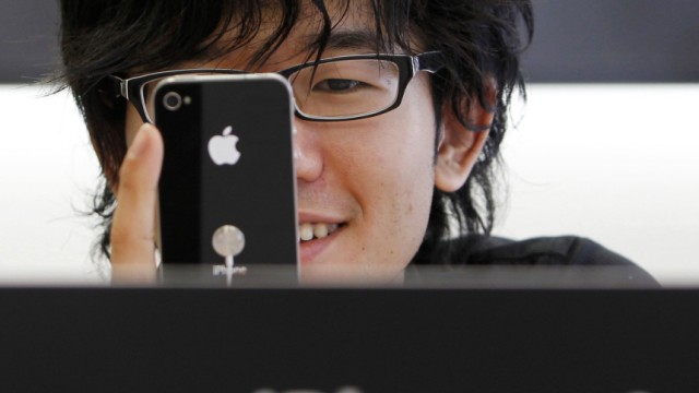 File photo of a customer trying out the new iPhone 4 at Apple Inc's store in the Ginza district of Tokyo