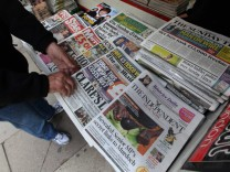 A man buys a Sunday newspaper at a news stand in London