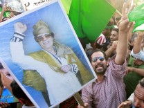 Supporters of Libya's leader Muammar Gaddafi take part in a rally in the town of al-Aziziyah
