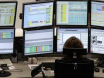 A trader is pictured at her desk in front of screens at the Frankfurt stock exchange