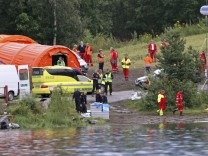 Rescue workers set up a camp across a lake, opposite the small, wooded island of Utoeya